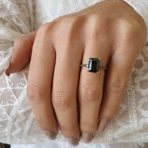emerald cut black diamond ring on finger